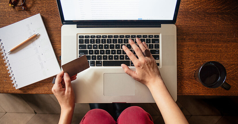 Overhead of woman on laptop with credit card