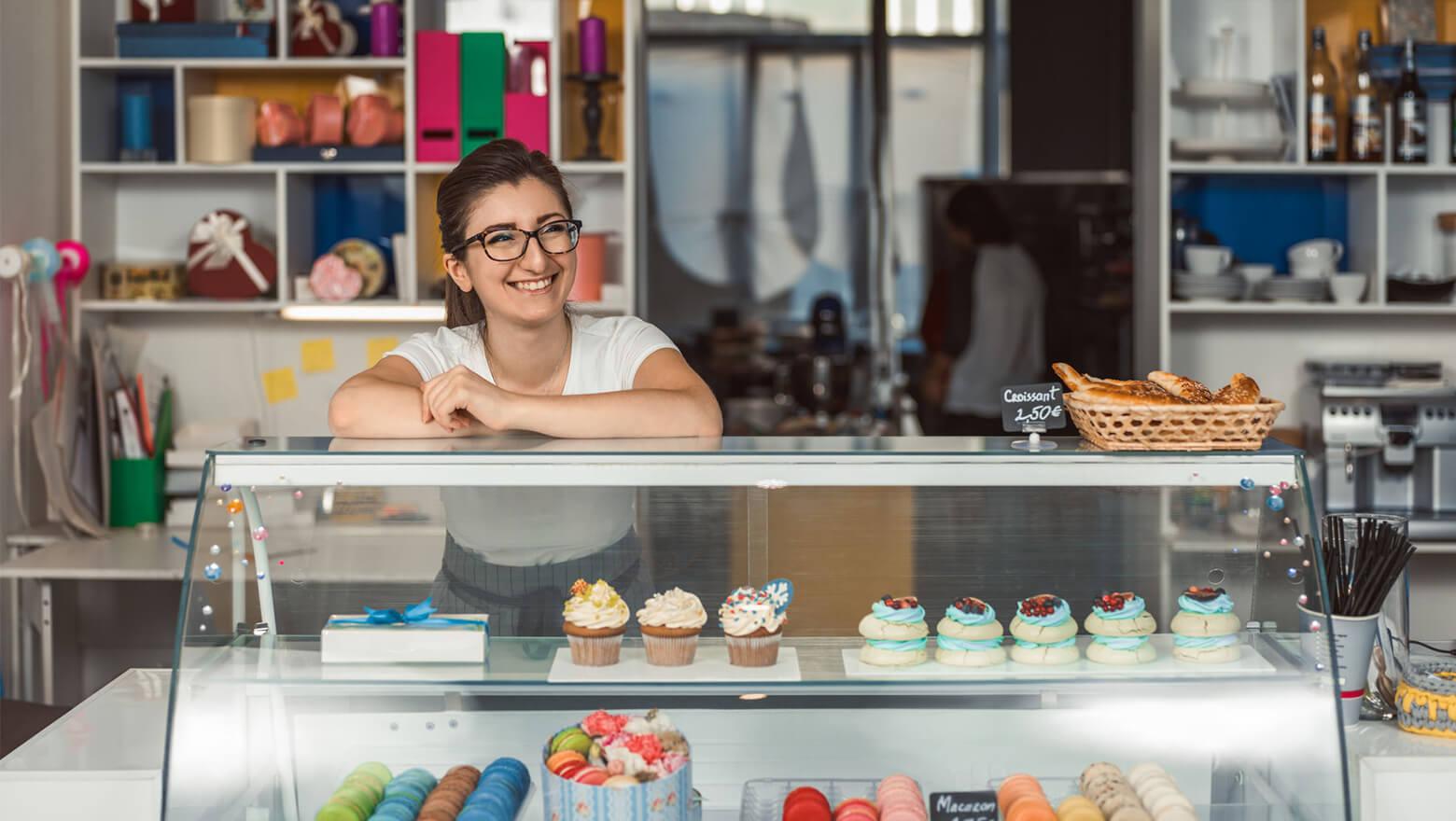 woman behind counter at a cupcake shop