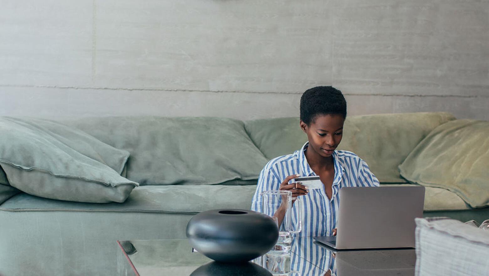 Woman using credit card at home