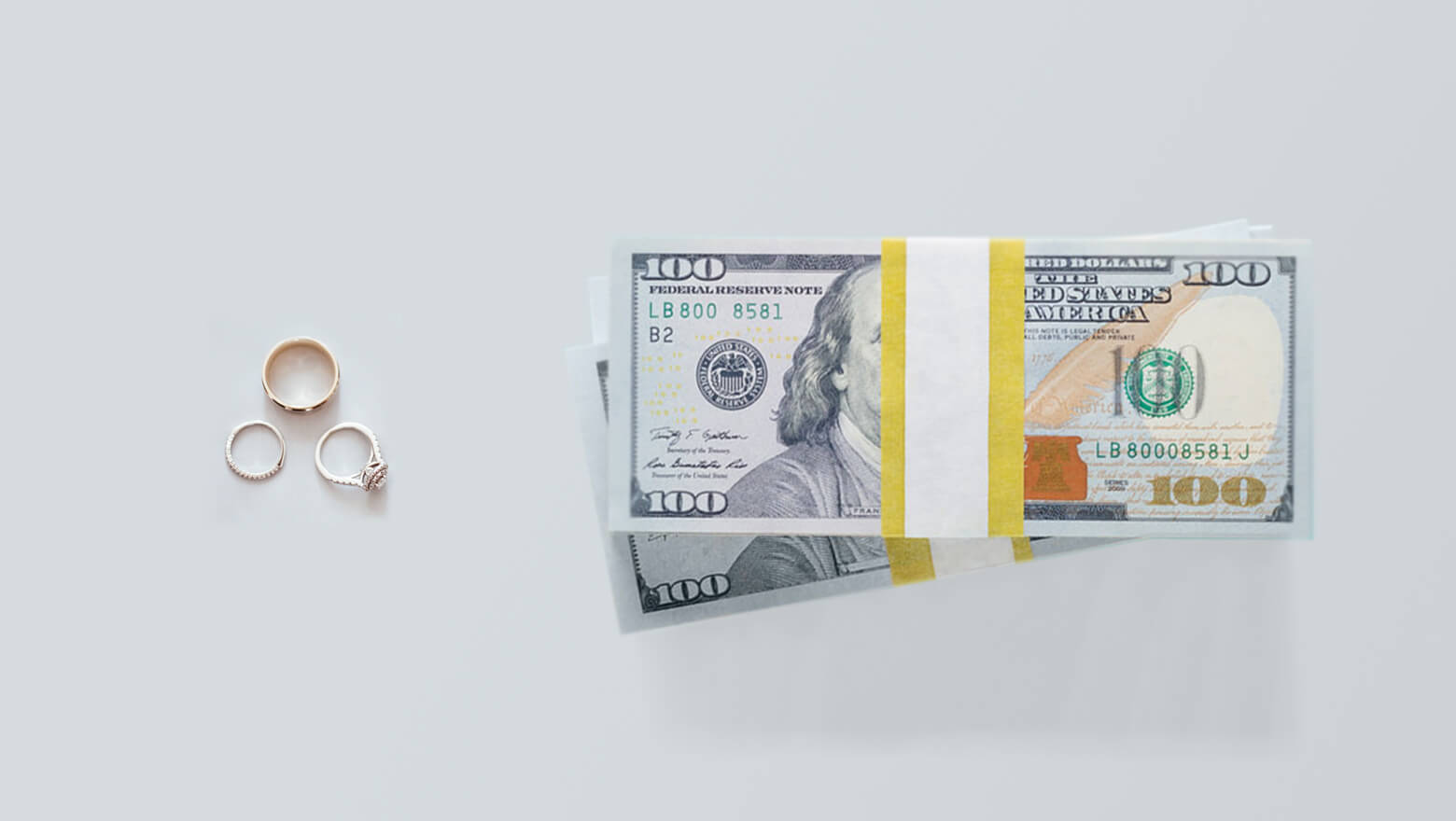 Stacks of cash with wedding rings