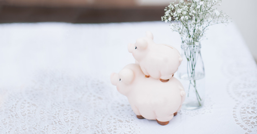 Stacked piggy banks on white tablecloth