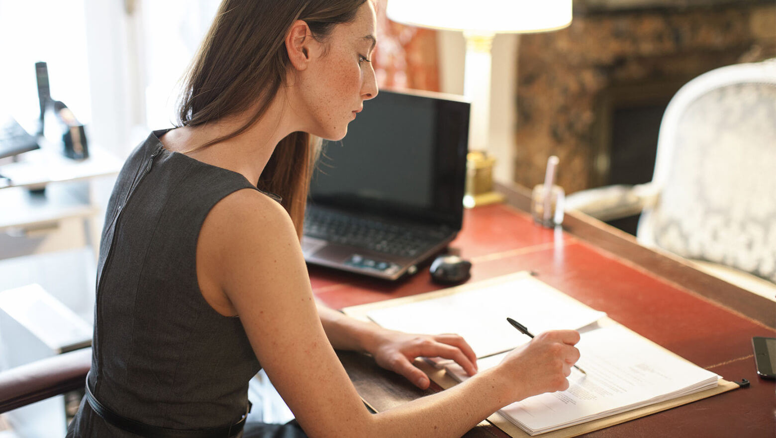woman reading documents in office