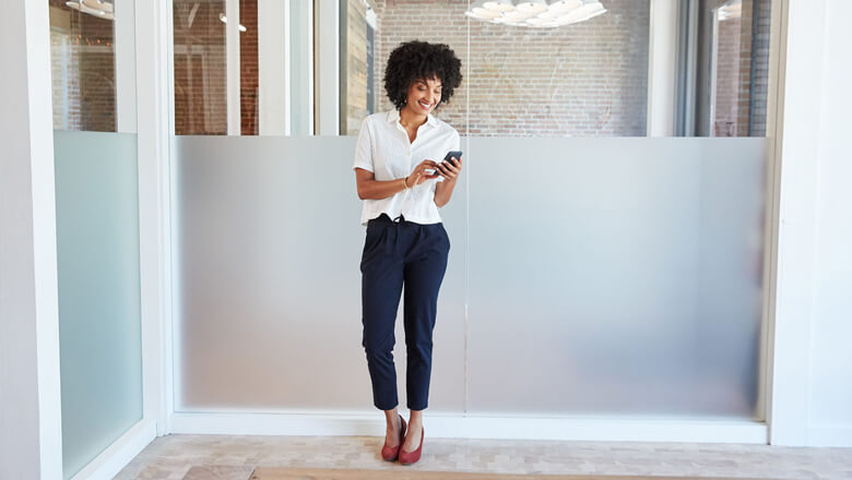 woman standing in office with smartphone