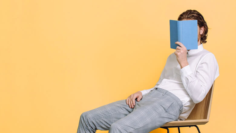 man with book orange background