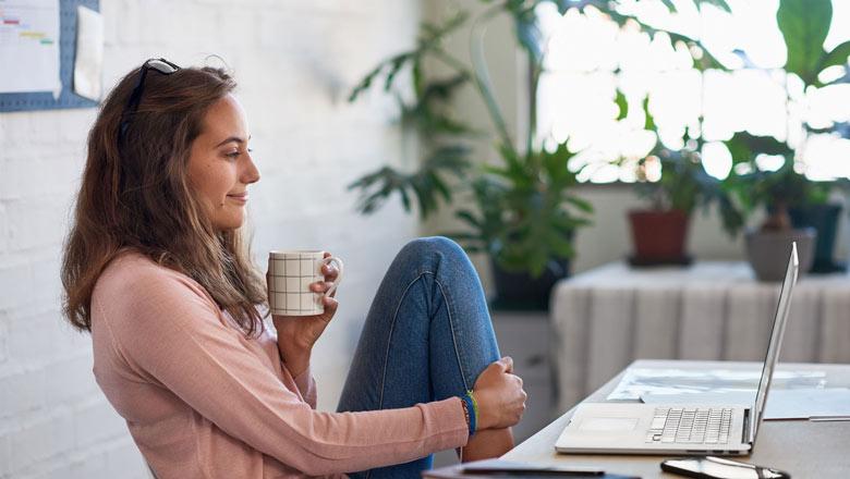 Woman with mug on laptop