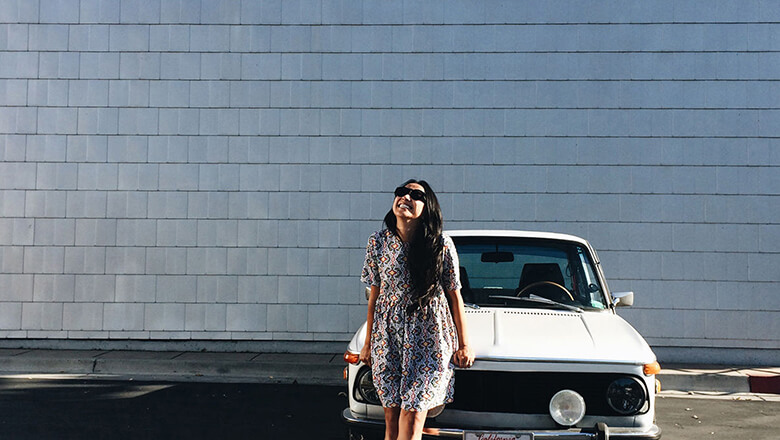 Woman smiling in front of car