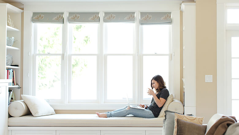 Woman on laptop at window seat