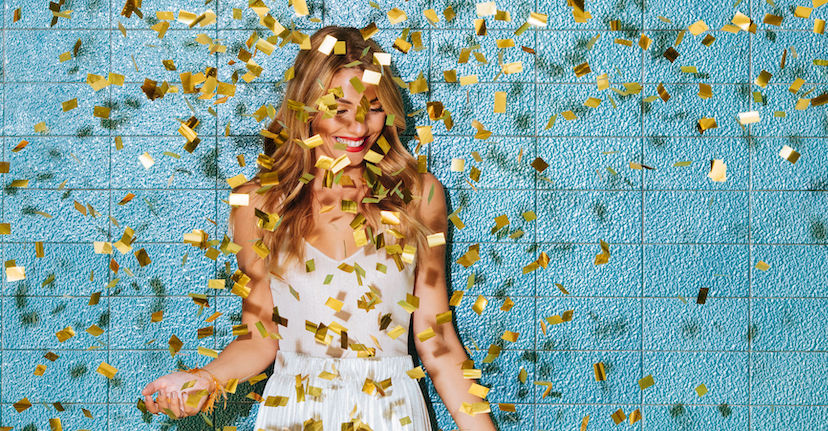woman smiling under falling confetti.