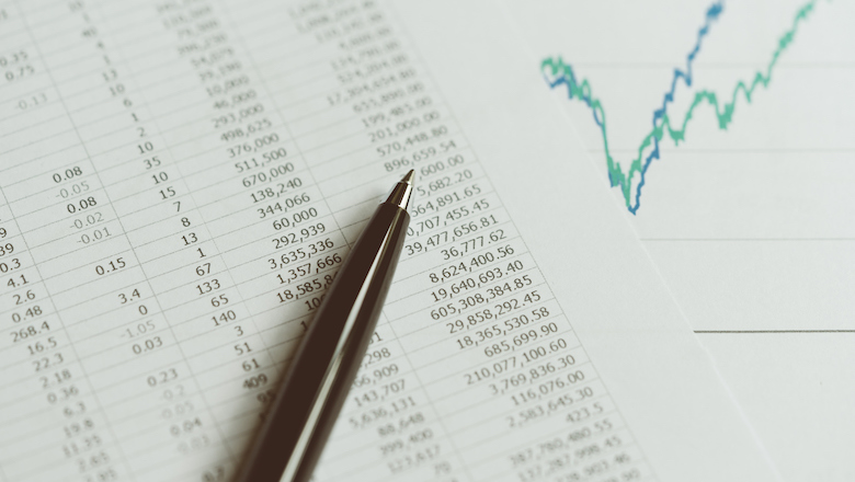 Investment, financial report statistic concept, close-up of black pen on printed stock exchange data price number or valuation table with green and blue yearly graph