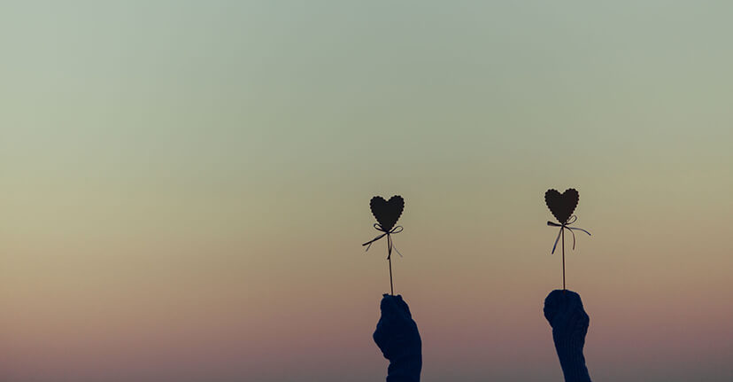 hands holding hearts on sticks