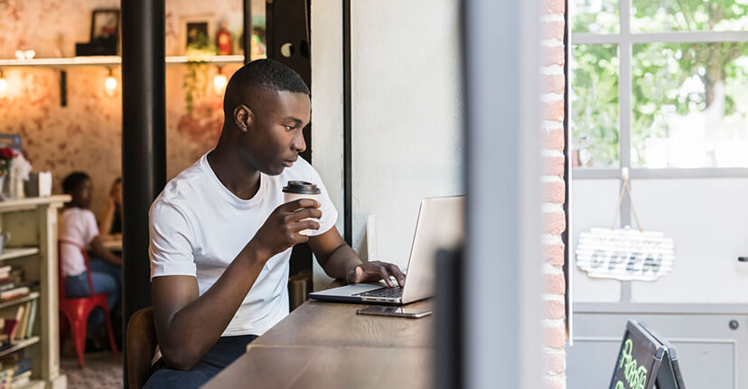man drinking coffee with laptop