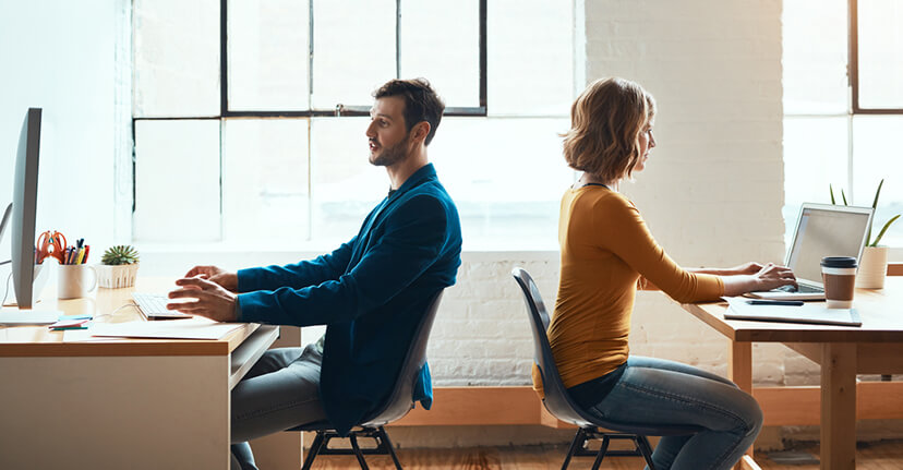 Man and woman in office back to back