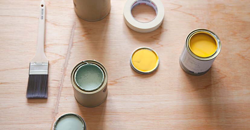 Paint cans and brush on wood floor