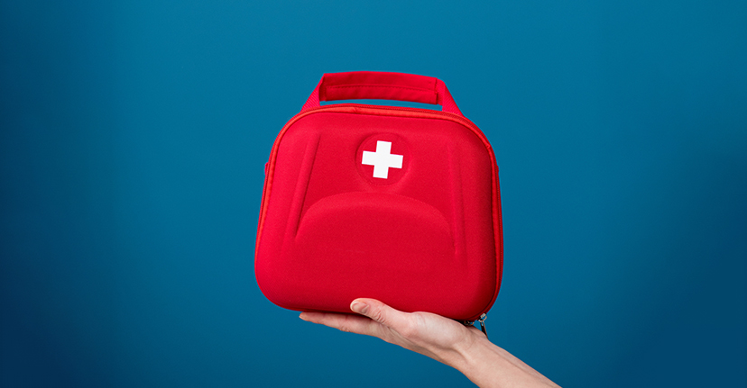 Red first aid kit on blue background