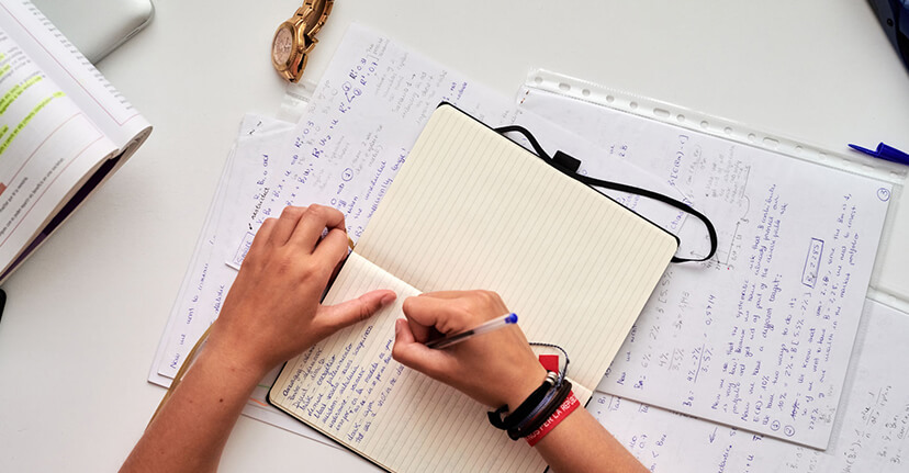 student working in notebook