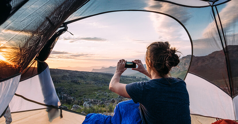 woman with smartphone in tent