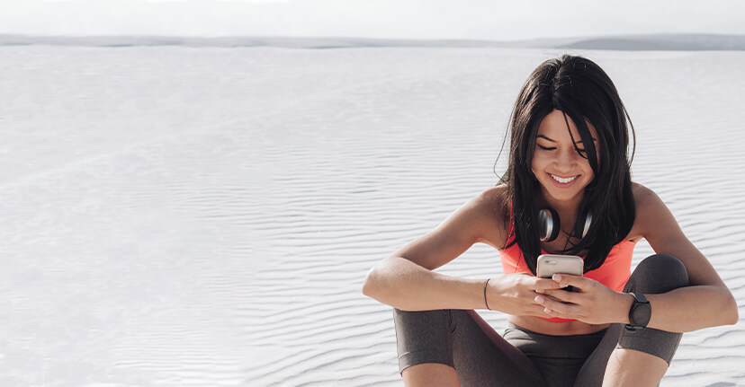 work out woman in sand with smartphone