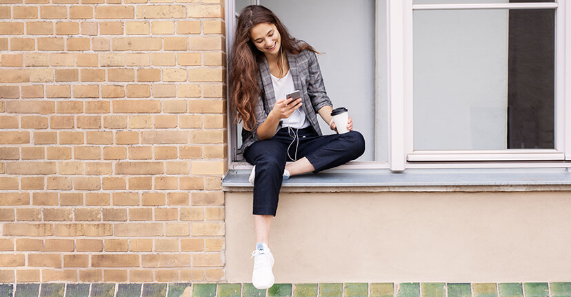 student sitting in window on phone
